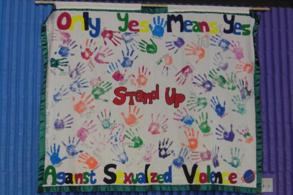 """Hand prints covering a banner: """"STand up"""""""