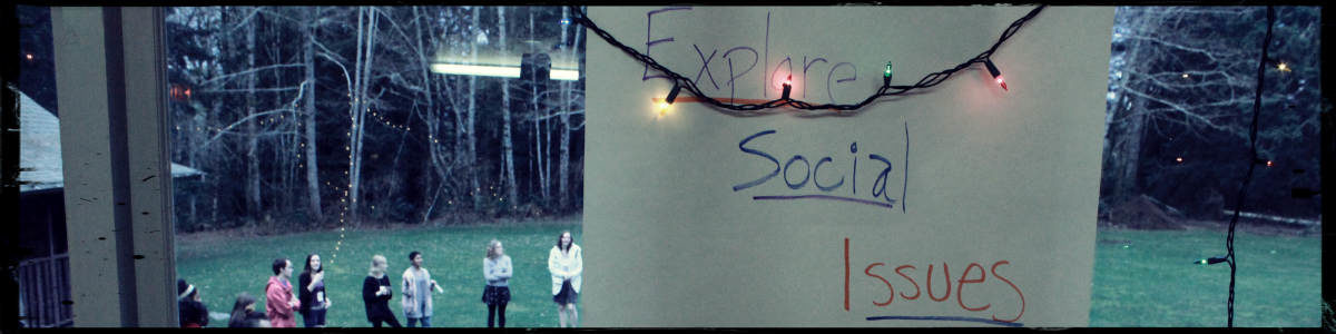 Explore Social Issues poster underneath lights, outside through the window people are standing in a circle
