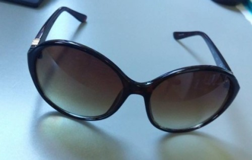 Brown sunglasses on grey surface.
