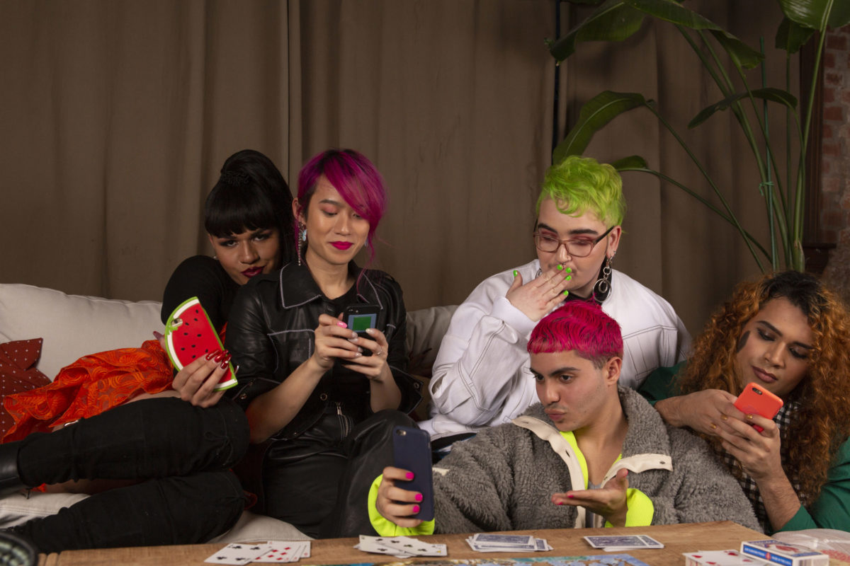A group of friends of varying genders taking selfies on cell phones.