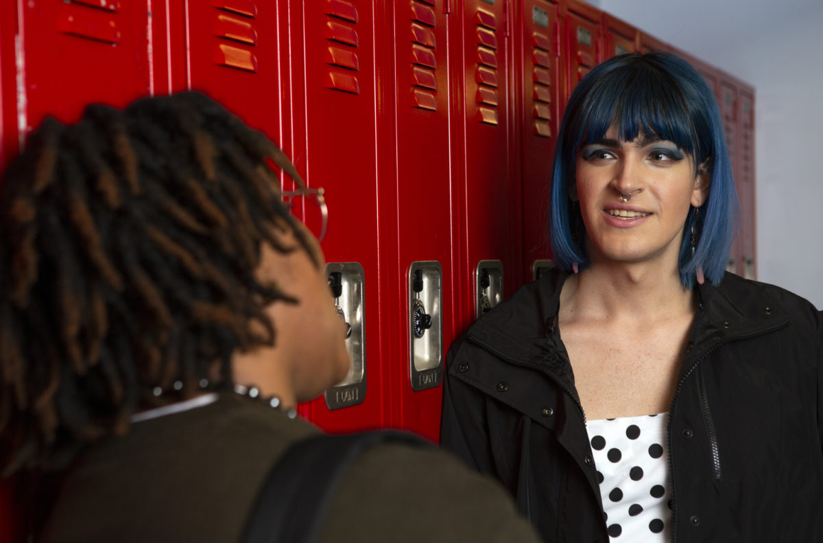 A non-binary femme student talking to a friend in front of their locker