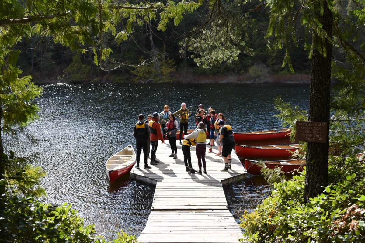 A group of youth with life jackets hang out on the dock before getting into the canoes at Glinz Lake.