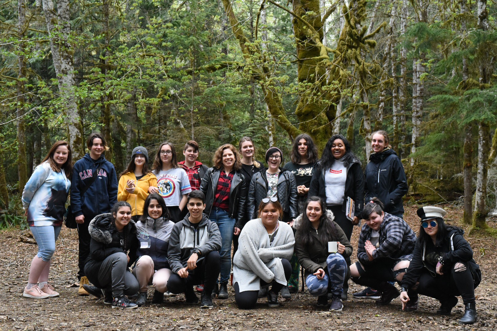 A group of twenty youth and adult staff pose as a group in a lush evergreen forest. They are all smiling at the camera.