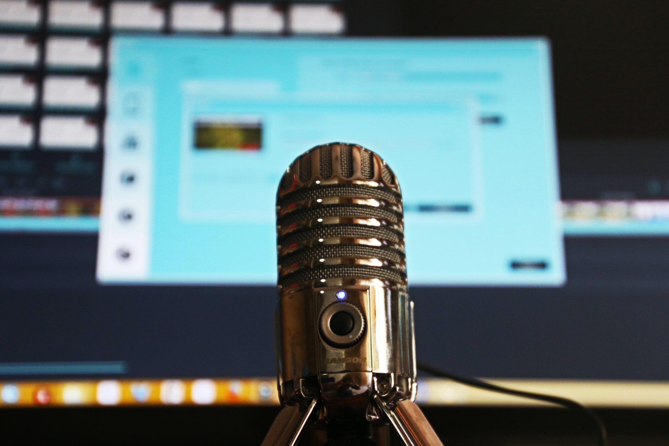 A photo of a microphone in front of a computer
