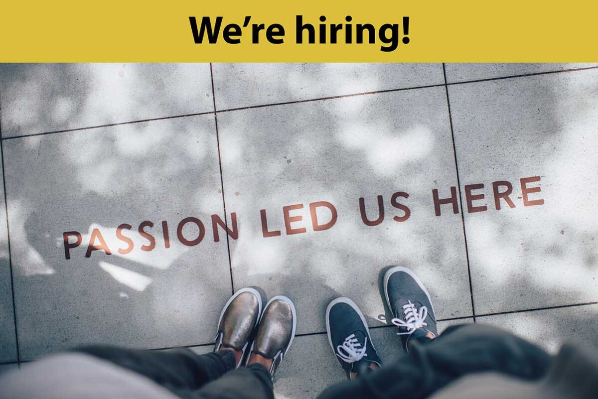 """A banner reads """"We're hiring!"""" above an image of pavement with the words 'passion led us here' printed on it, and two pairs of feet at the bottom."""