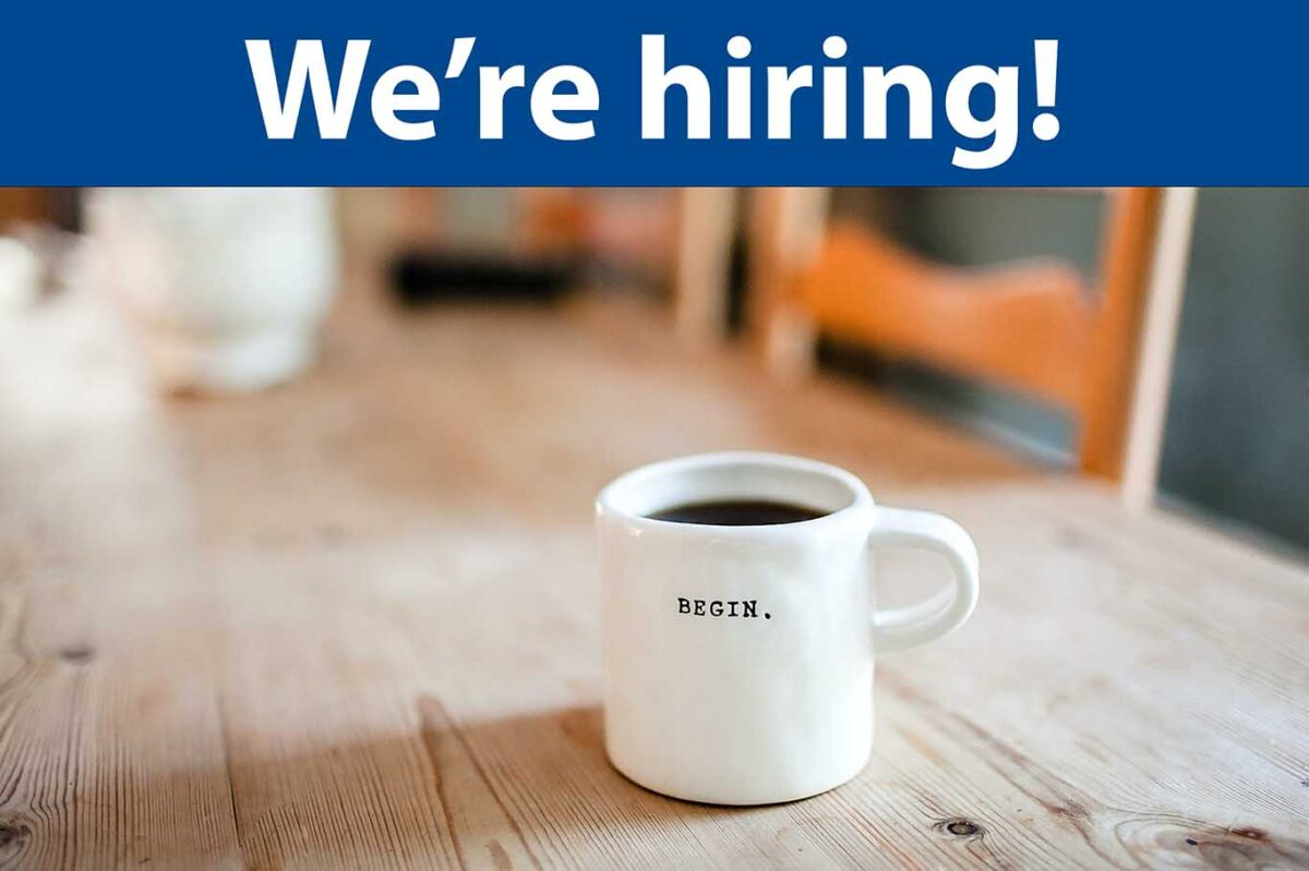 """A banner reads """"We're hiring!"""" above an image of a mug of coffee on a wooden table. The mug has the word Begin imprinted on it."""